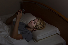 Young woman unable to sleep on cell phone in bed